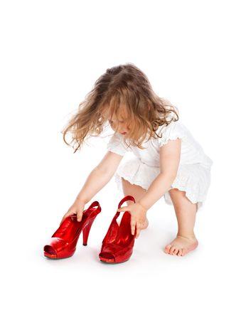 piedi nudi di bambine: Little girl in abito bianco con grandi scarpe rosse. Isolated on white background Archivio Fotografico