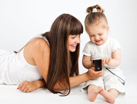 Mother  and little daughter speaking by phone. Gray background photo