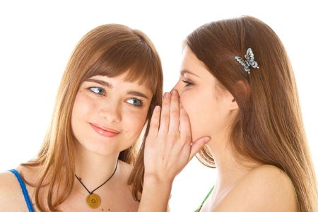 Two happy young girlfriends telling secrets. Isolated on white background photo