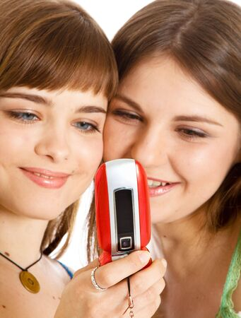 Two pretty girls reading SMS on mobile phone. Isolated on white background Stock Photo - 5318890
