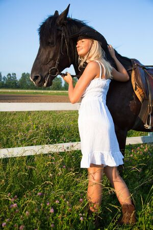 Young blond woman in white dress  with horse photo