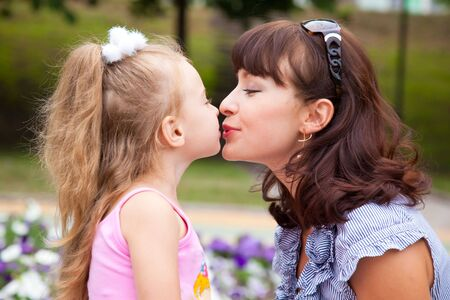Mother is kissing daughter in a park photo