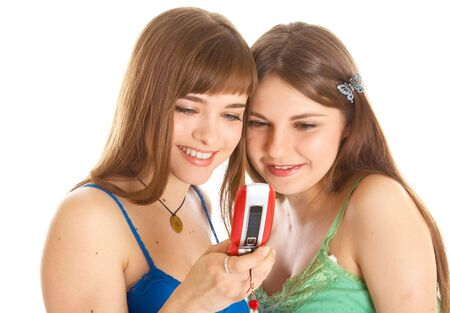 Two pretty girls reading SMS on mobile phone. Isolated on white background Stock Photo - 5318923