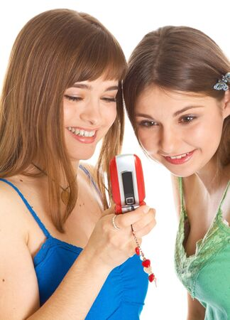 Two pretty girls reading SMS on mobile phone. Isolated on white background photo