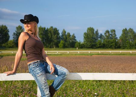 Young cowgirl sitting on a white fence photo