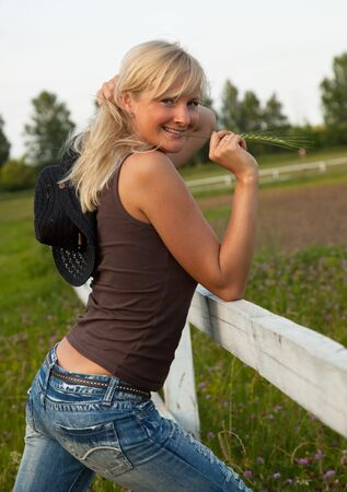 cute young farm girl: Young cowgirl stand near a white fence Stock Photo