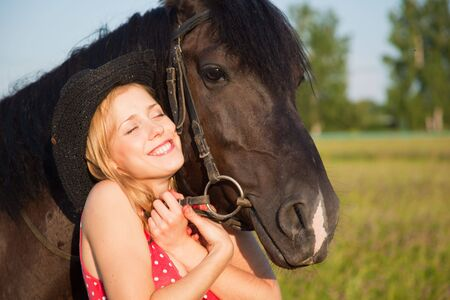 Young blond woman in red dress  with horse photo