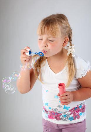 blow out: Blow ragazza giovane la formazione di bolle di sapone su sfondo grigio