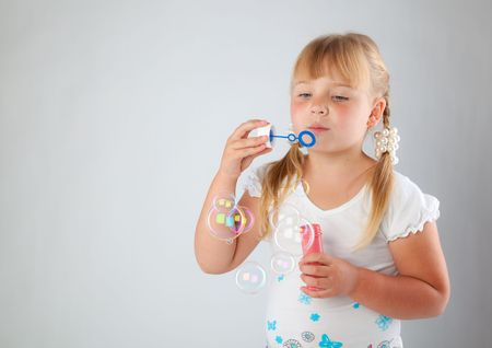 blow out: Young girl blow out soap bubbles on gray background
