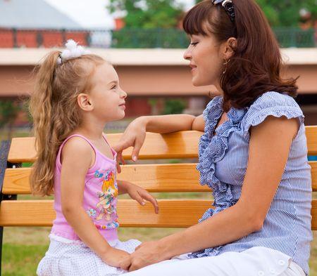 padres hablando con hijos: Madre e hija en un parque Foto de archivo