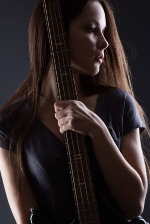 Woman with electric guitar on gray background photo