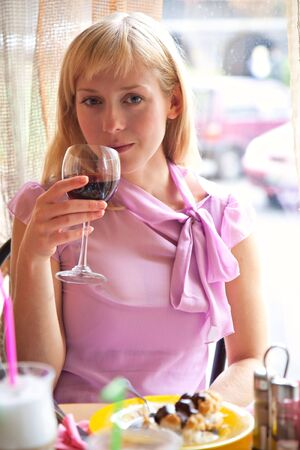Young girl is drinking wine in cafe photo