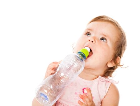 Little girl is drinking from bottle. Isolated on white background photo