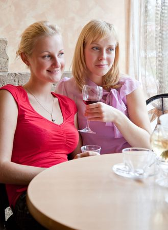 Two young girls are drinking wine in cafe photo