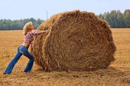 bale: Young woman is pushing bale of straw