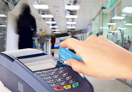 business transaction: Human hand holding plastic card in payment machine in shop