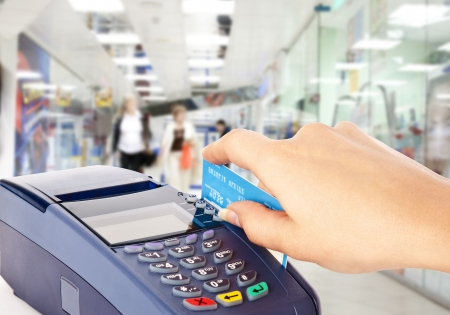 card payment: Human hand holding plastic card in payment machine in shop