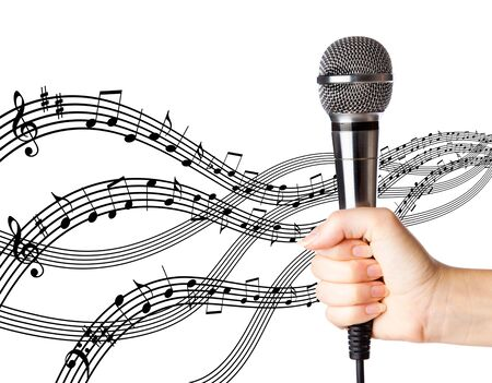 Hand with microphone on background with notes photo