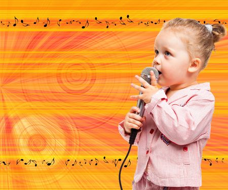 Little girl with microphone on background with notes photo