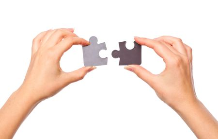 Hands with two puzzles. Isolated on white background photo
