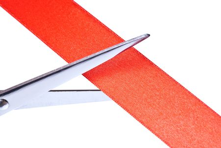 Scissors cutting red ribbon.  Isolated on white background photo