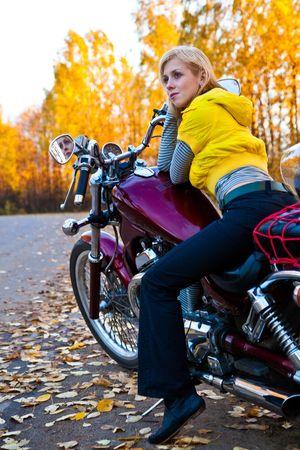 Young beautiful girl on motorcycle. Autumn photo