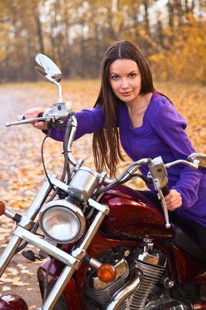 Young beautiful female biker on motorcycle. Autumn photo