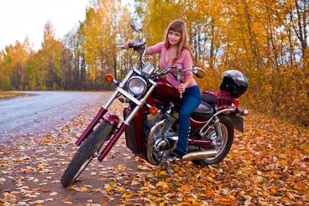 Young beautiful girl on motorcycle. Autumn photo