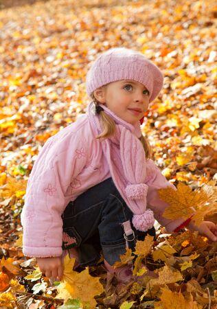 Little girl in autumn park photo