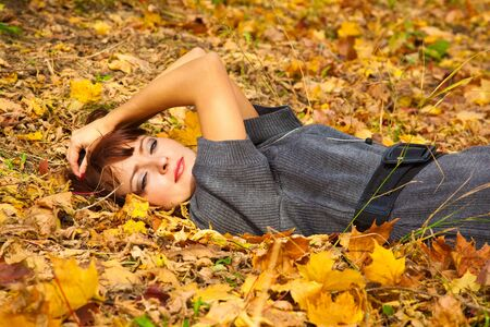 Young woman is lying in leaves photo