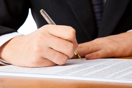 Close up on a businessman hands signing a contract. Isolated on white background Stock Photo - 6165964