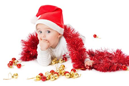 Little boy wearing a Santa hat and playing with baubles. Isolated on white background photo