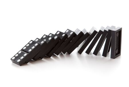 domino effect: Stack of dominoes falling. Isolated on a white background