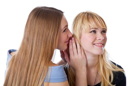 Two happy young girlfriends telling secret. Isolated on white background photo