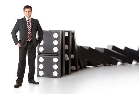 business activity: Businessman near a stack of dominoes. Isolated on white background