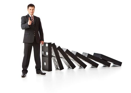 domino: Businessman near a stack of dominoes. Isolated on white background