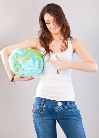 student travel: Girl with globe on gray background