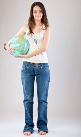 Girl with globe on gray background photo