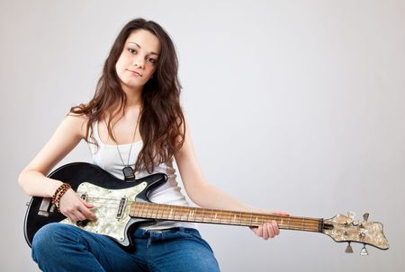 Teenage girl  with electric guitar on gray background photo