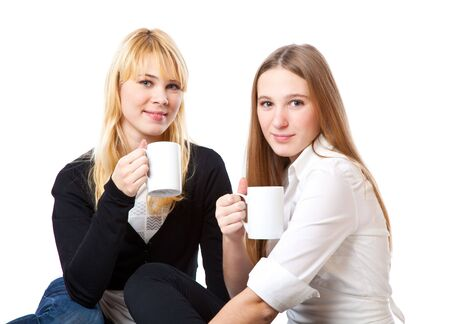 Two teenage girls is drinking tea. Isolated on white background photo