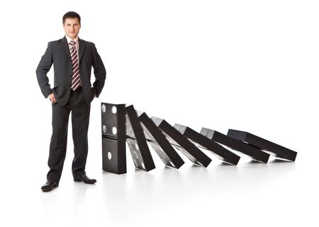 Businessman near a stack of dominoes. Isolated on white background photo