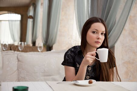 Young girl is drinking coffee in cafe photo