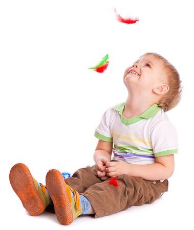 bambin: Petit gar�on est assis sur un flux avec des plumes. Isol� sur fond blanc