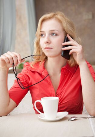 Young blond girl in cafe is drinking coffee and is speaking by mobile phone photo