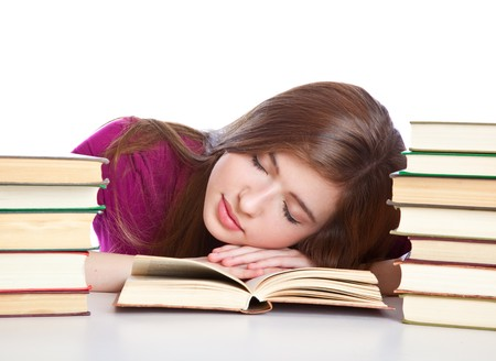 Meisje �t th� d�sk zitten en slapen op een boek. Geïsoleerd op witte achtergrond  Stockfoto
