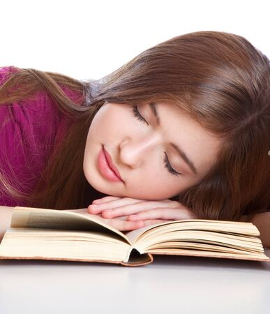 Young girl sitting àt thå dåsk and sleeping on a book. Isolated on white background Stock Photo - 7011283