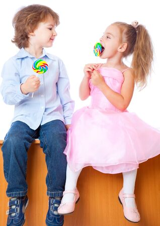 Boy and girl with lollipops. Isolated on white background photo