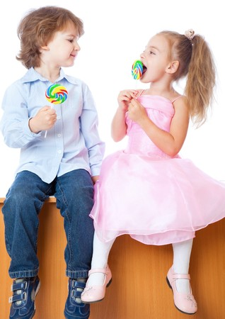 little table: Boy and girl with lollipops. Isolated on white background