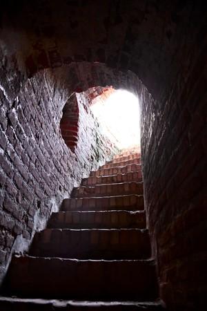 end line: Luz al final de una escalera en una antigua torre