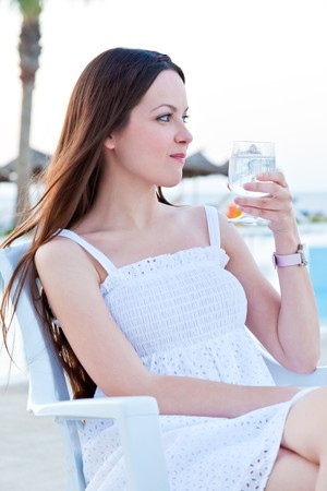 Woman in white dress with wine near a pool photo